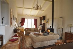 very large, comfortable sitting room with Jotul woodburner and large glazed doors leading to terrace
