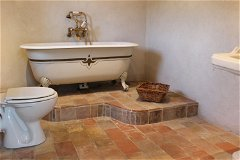 Bathroom 3 with antique roll-top claw-feet bath and brass shower unit.