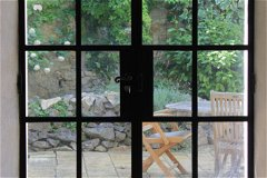 The metal framed, double glazed double door leading from the dinning room to the courtyard.