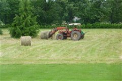 Farmer removing 2 Bales of hay from garden
