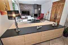 Open plan living area with feature wall & stove