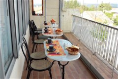 Breakfast terrace with sliding glass wall and second window giving 180 degree views